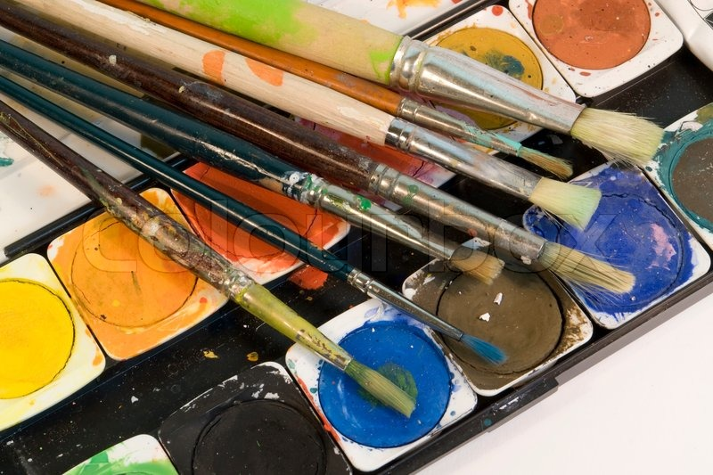 Stock image of 'Detail shot showing a used set of watercolors and some paintbrushes'