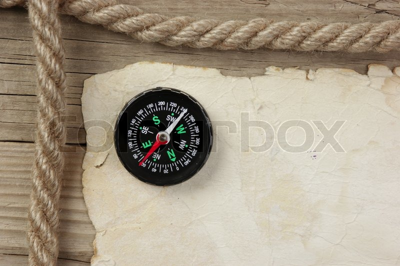 Vintage paper with compass and rope on old wooden boards, stock photo