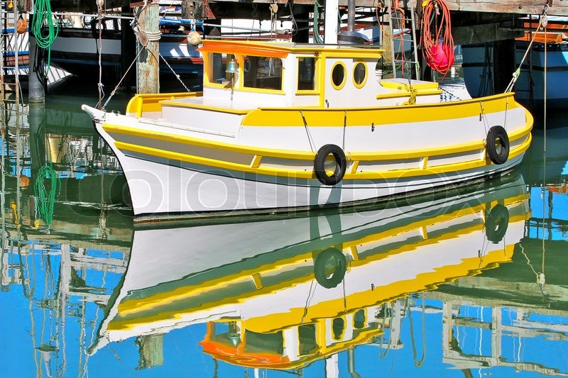 Yellow and white fishing boat moored at dock and reflected with blue ...