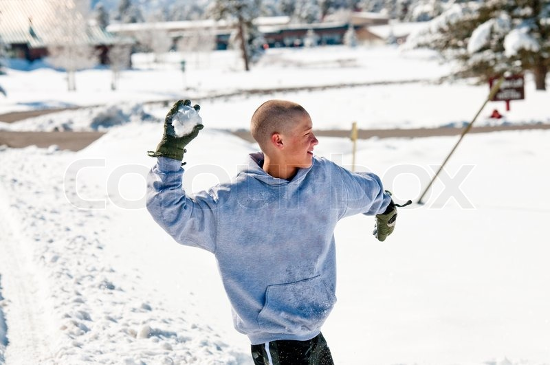 happy bald boy wearing a hood throwing a snowball