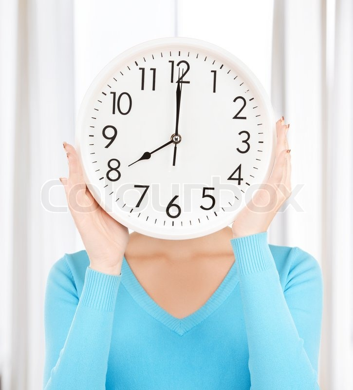 Businesswoman with clock over her face, stock photo