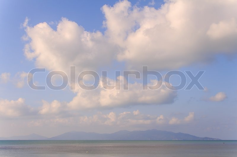 Seascape with puffy heart clouds,sand and blue sky, stock photo