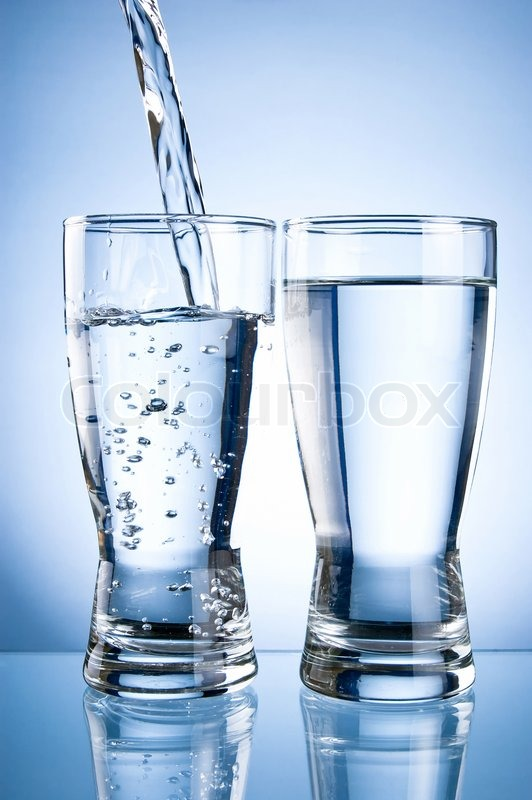 Pouring water into glasson and Glass of water on a blue background, stock photo