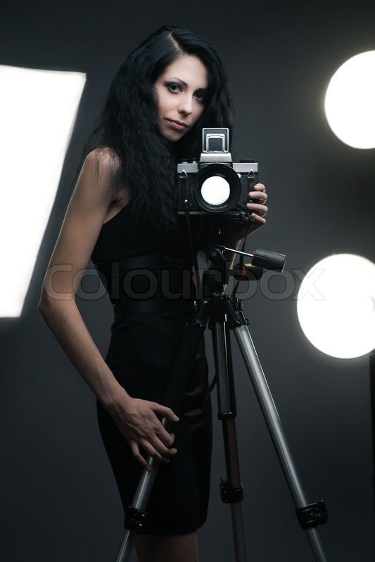 Stylish woman photographer in studio with light accessories on b, stock photo