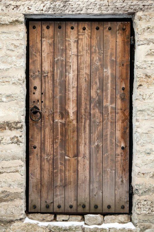 Ancient Wooden Door In Old Stone Castle Wall Tallinn