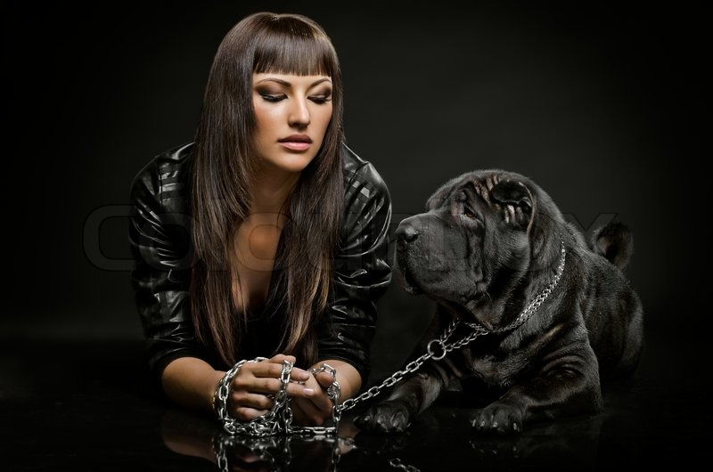 The beautiful young woman sit with dog on black background, stock photo