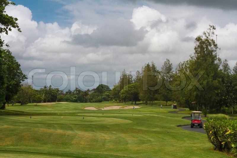 Red car on golf courses, and the sky in the clouds, stock photo