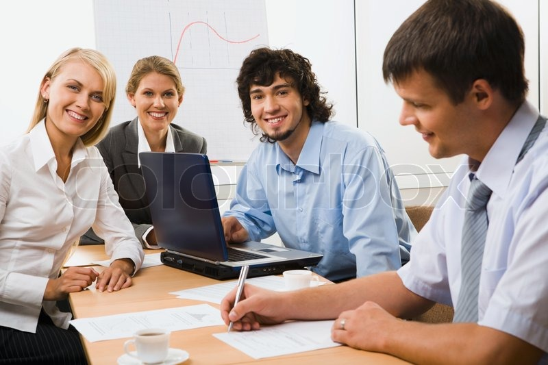 Stock image of 'Portrait of four young business people sitting around the table with documents, papers, pen, cup of coffee and opened laptop on it and a diagram behind them'