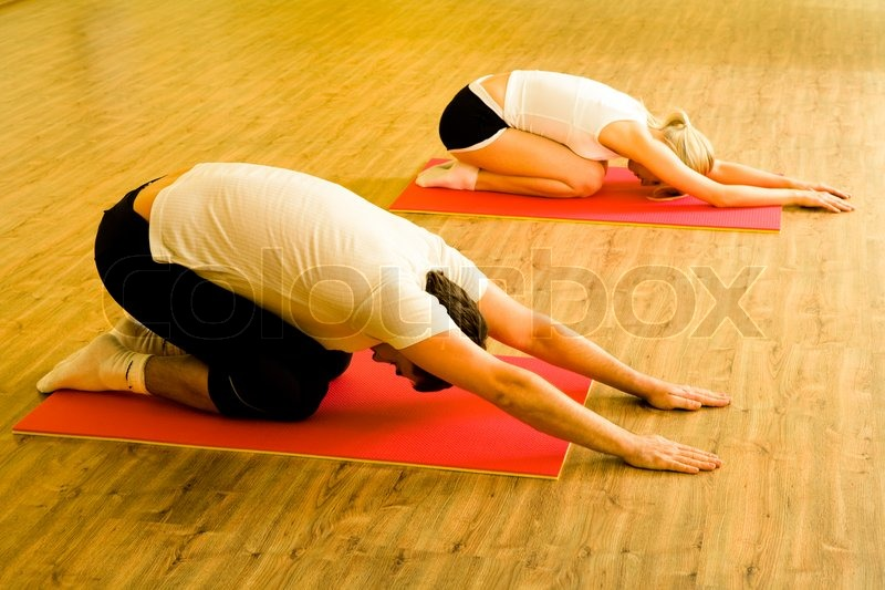 Image of man and woman doing physical exercises on mats in the sports club together, stock photo