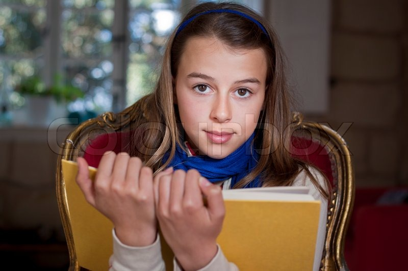A young girl holding up a book, looking at camera, Real people, candid shot, stock photo