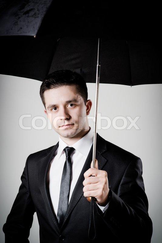 business man holding an umbrella stock photo colourbox