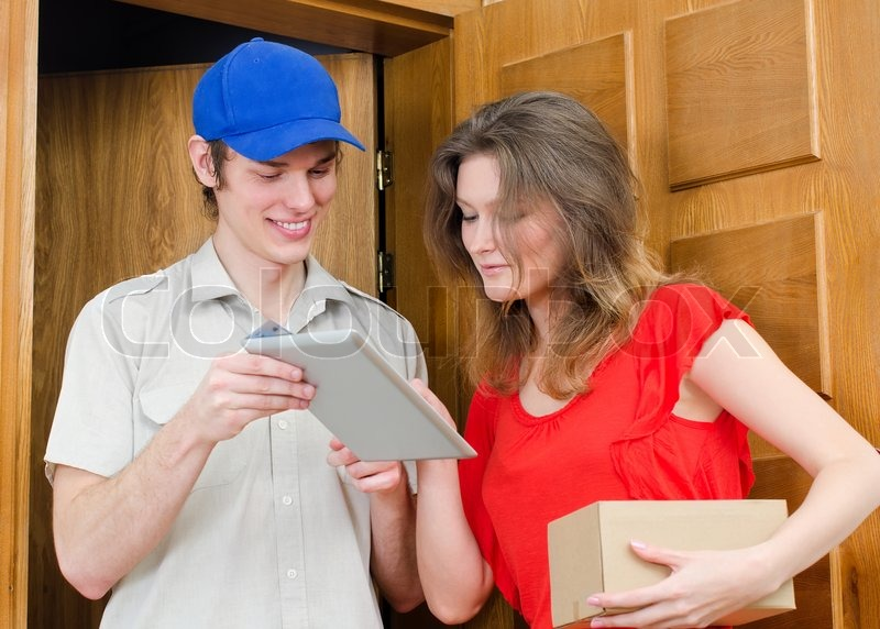 Young courier deliver package to pretty woman, stock photo