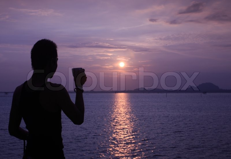 Silhouette of relaxing man having coffee while sun rising, stock photo
