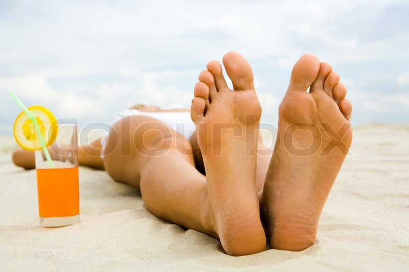 Stock image of 'Close-up of two human feet on sandy beach with cocktail near by'