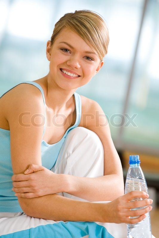 Portrait of lovely girl holding bottle of water in hand and smiling, stock photo
