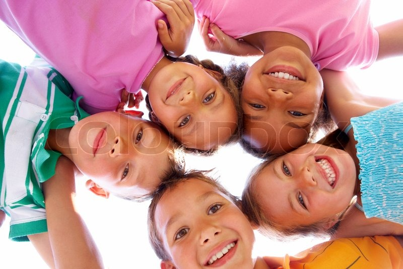 Stock image of 'Below view of happy children embracing each other and smiling at camera'