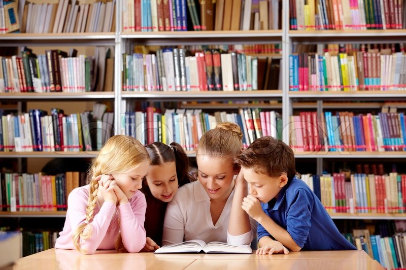 Stock image of 'Portrait of pupils and teacher looking at page of interesting book in library '