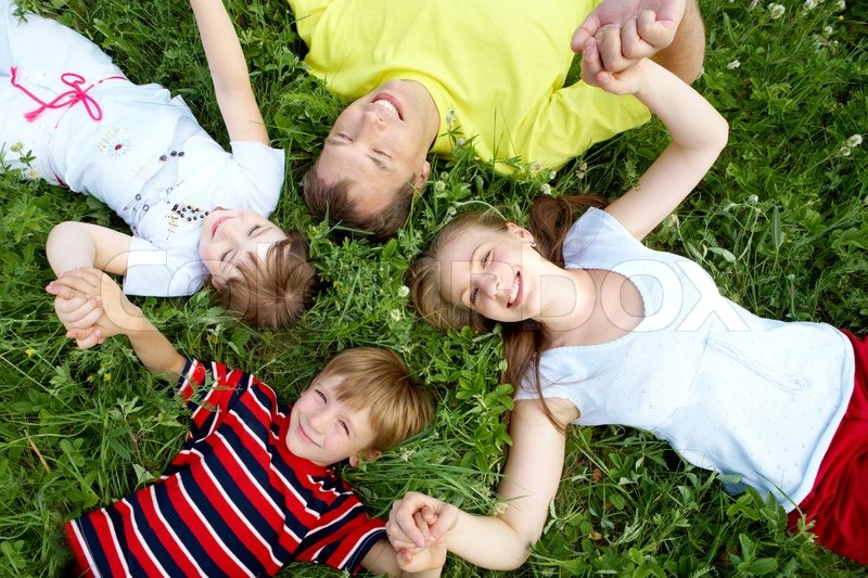 Stock image of 'View from above of relaxing people lying on grass of meadow during rest'