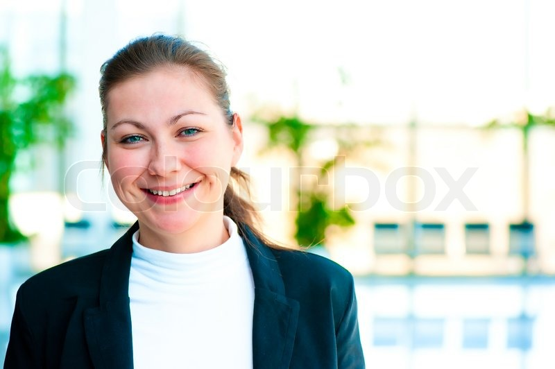 Portrait of a smiling girl on the background of the manager de-focus office interior, stock photo