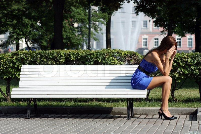 Young woman sitting on a park bench | Stock Photo | Colourbox