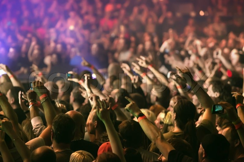 Crowd cheering and hands raised at a live music concert, stock photo