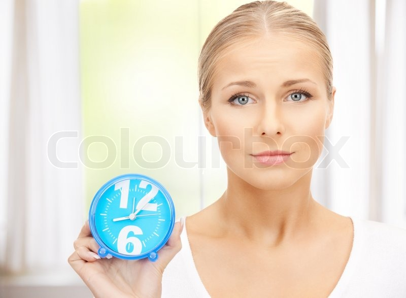 Bright picture of woman holding alarm clock, stock photo