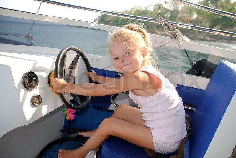 Little girl driving a sea boat, stock photo