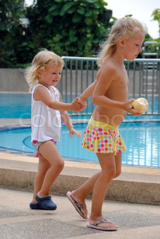 two little sisters walking around the pool | stock photo | colourbox