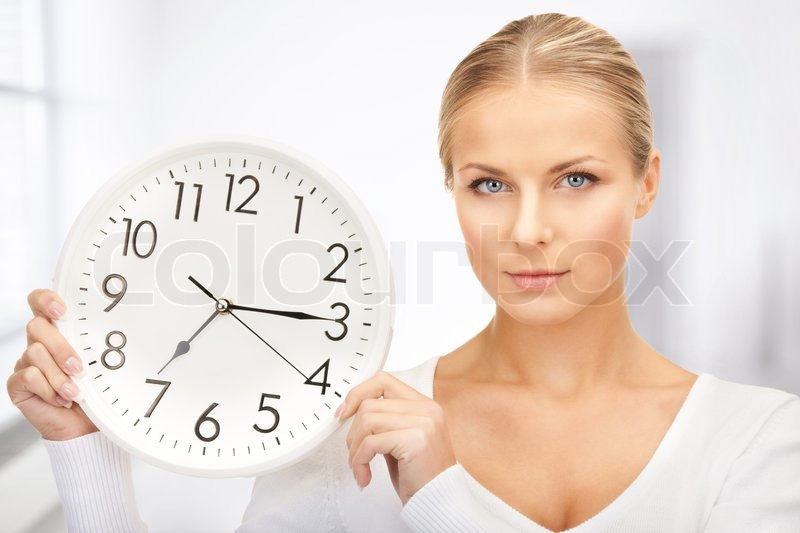 Picture of woman holding big clock in office, stock photo