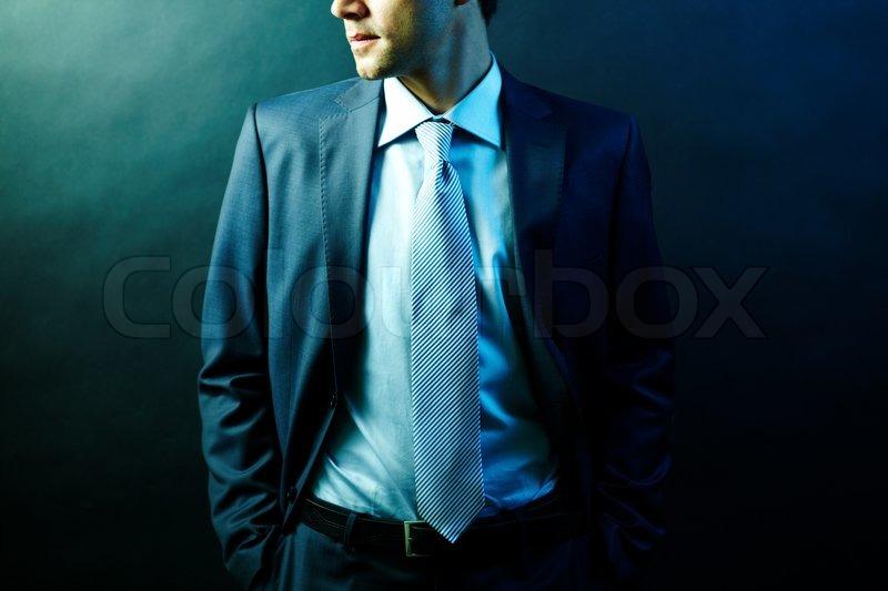 Figure of elegant businessman in suit posing in darkness, stock photo
