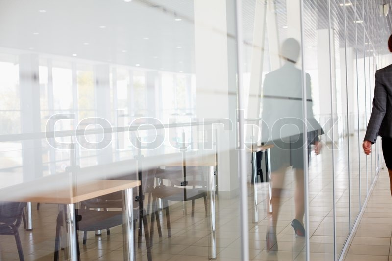Stock image of 'Reflection of businesswoman walking along the office corridor'