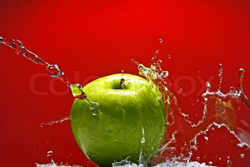 Green apple with water splash on red background, stock photo