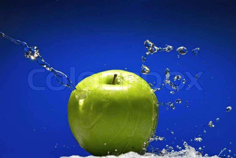 Green apple with water splash on blue background, stock photo