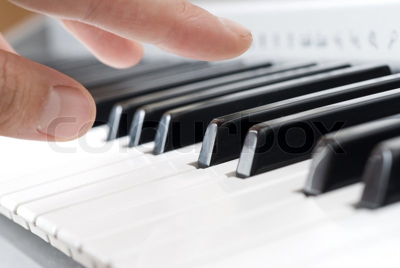Hand playing music on the piano, stock photo