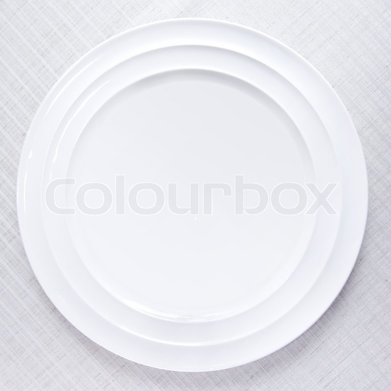 Empty white plate on tablecloth, stock photo
