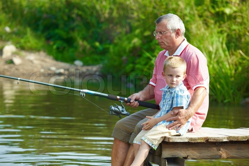 Stock image of 'Photo of grandfather and grandson sitting on pontoon and fishing on weekend'