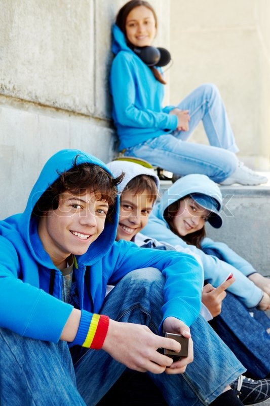 Stock image of 'Portrait of several teens looking at camera while spending time outdoors'