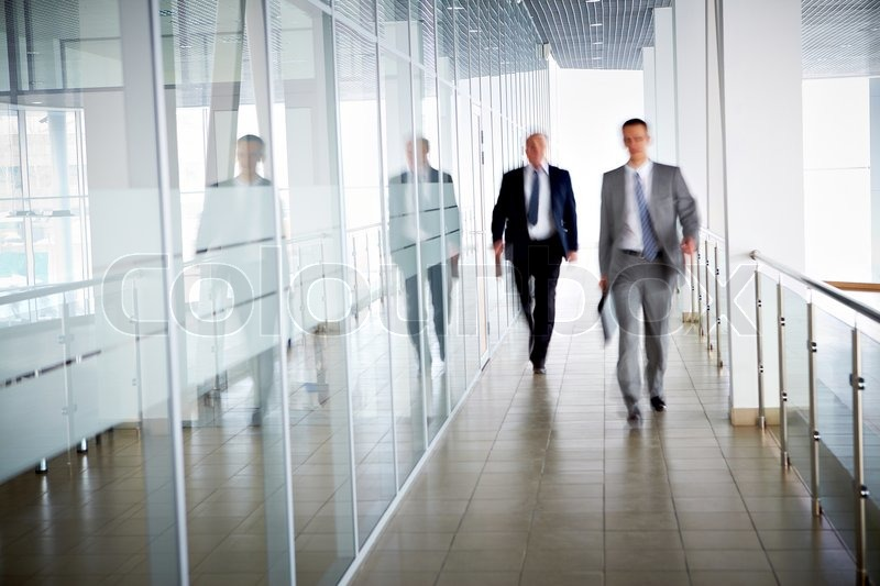 Business people walking in the office corridor, stock photo