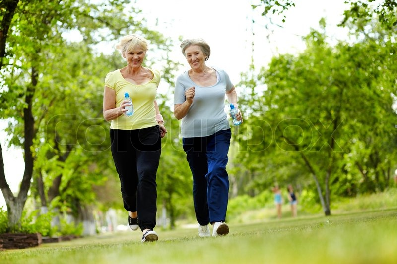 Stock image of 'Portrait of two senior females running outdoors'