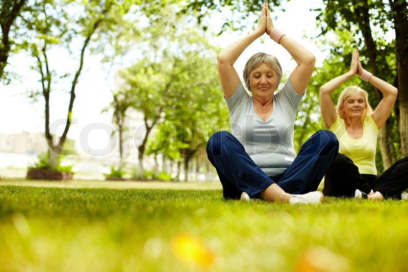 Portrait of two aged females doing yoga exercise on green grass, stock photo