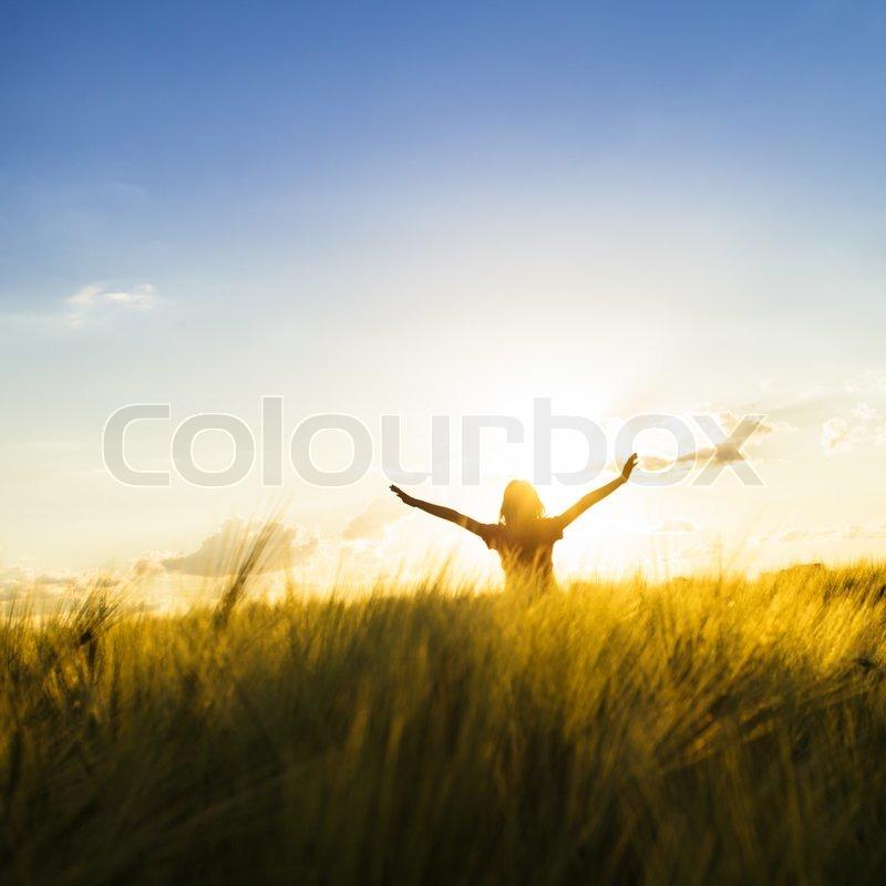 Teenage girl enjoy with sunshine in wheat field, stock photo