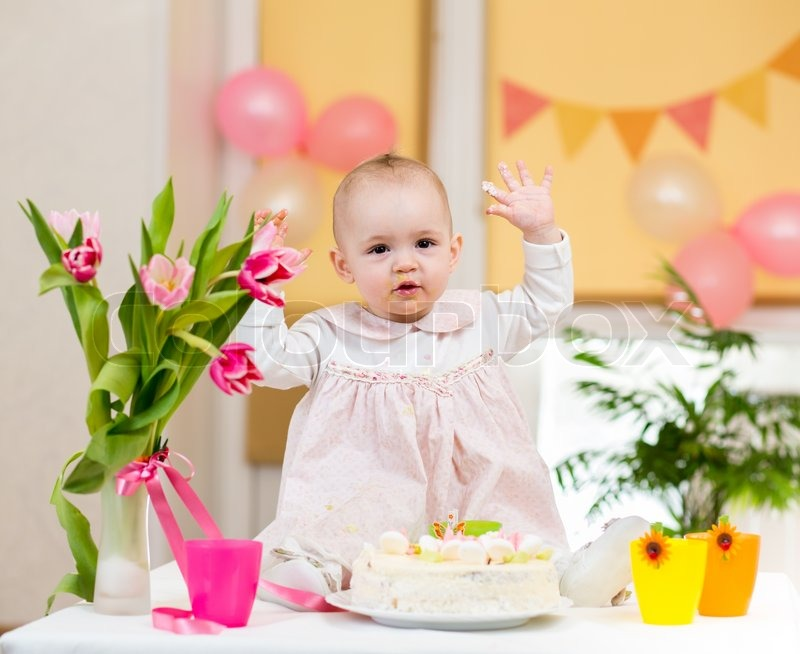 Baby girl celebrating first birthday and eating cake  Stock Photo ...
