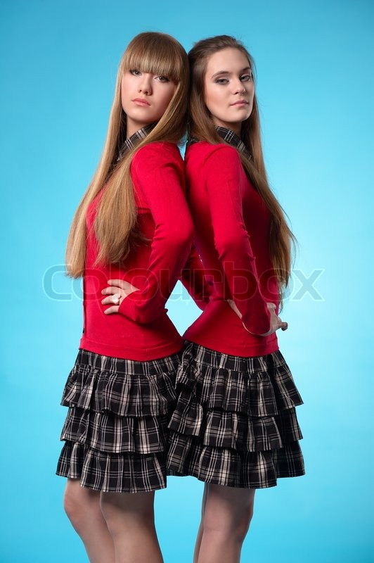 Two Teen Schoolgirls Stand Back To Back Over Blue Background Stock Photo Colourbox