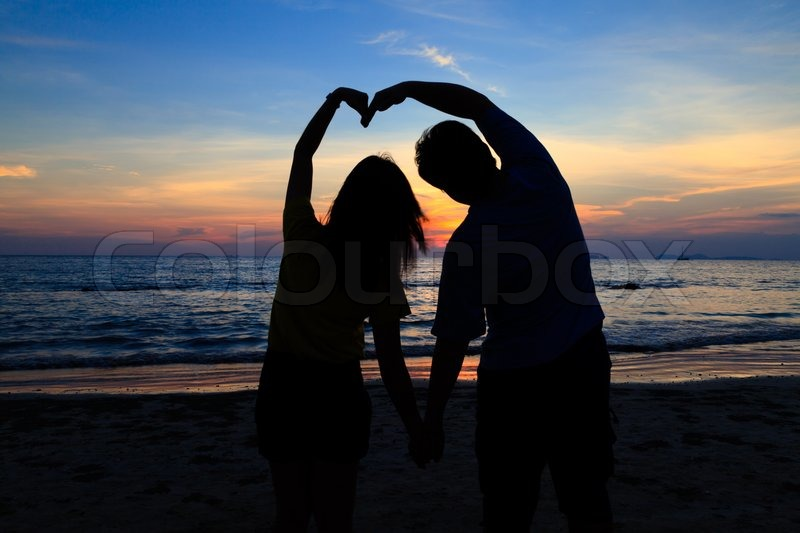Asian Boy And Girl With Heart Shape On The Sunset Beach