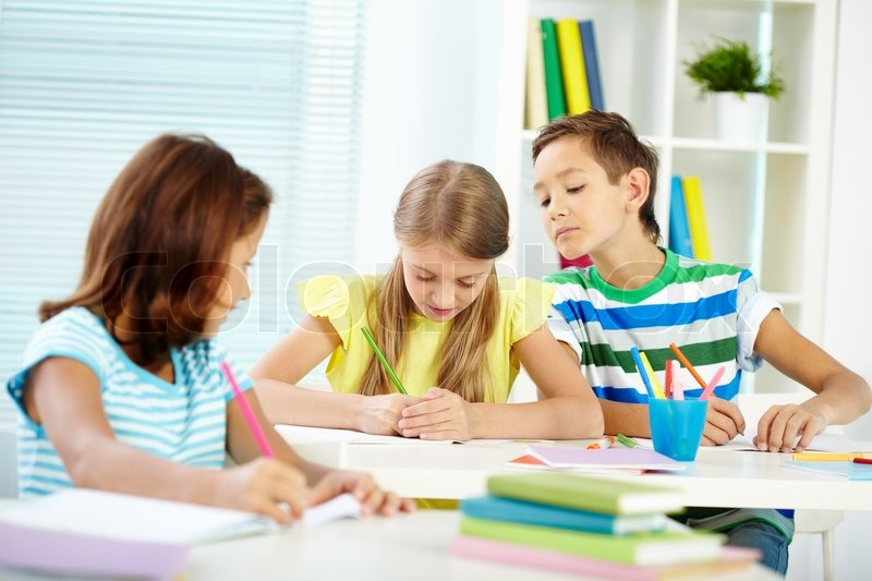 Portrait of cute schoolkids drawing at lesson, stock photo