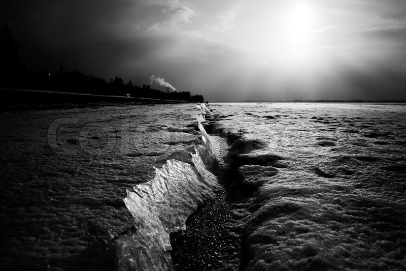 Dramatic frozen river landscape, black and white, stock photo
