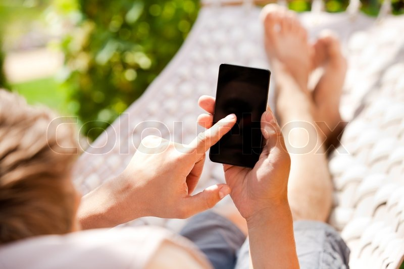 Man using mobile smart phone while relaxing in a hammock, stock photo