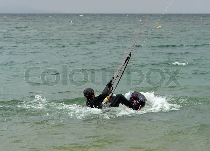 Holiday scenery in France with a kite surfing man while starting out of the water, stock photo