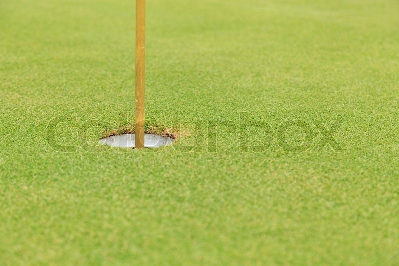 Golf hole and flag on green grass, stock photo