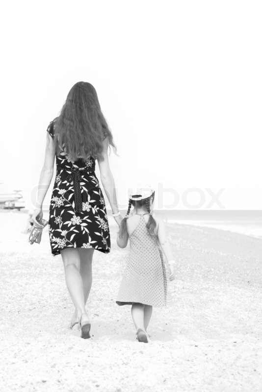 Mother and daughter walking on beach Black and white, stock photo
